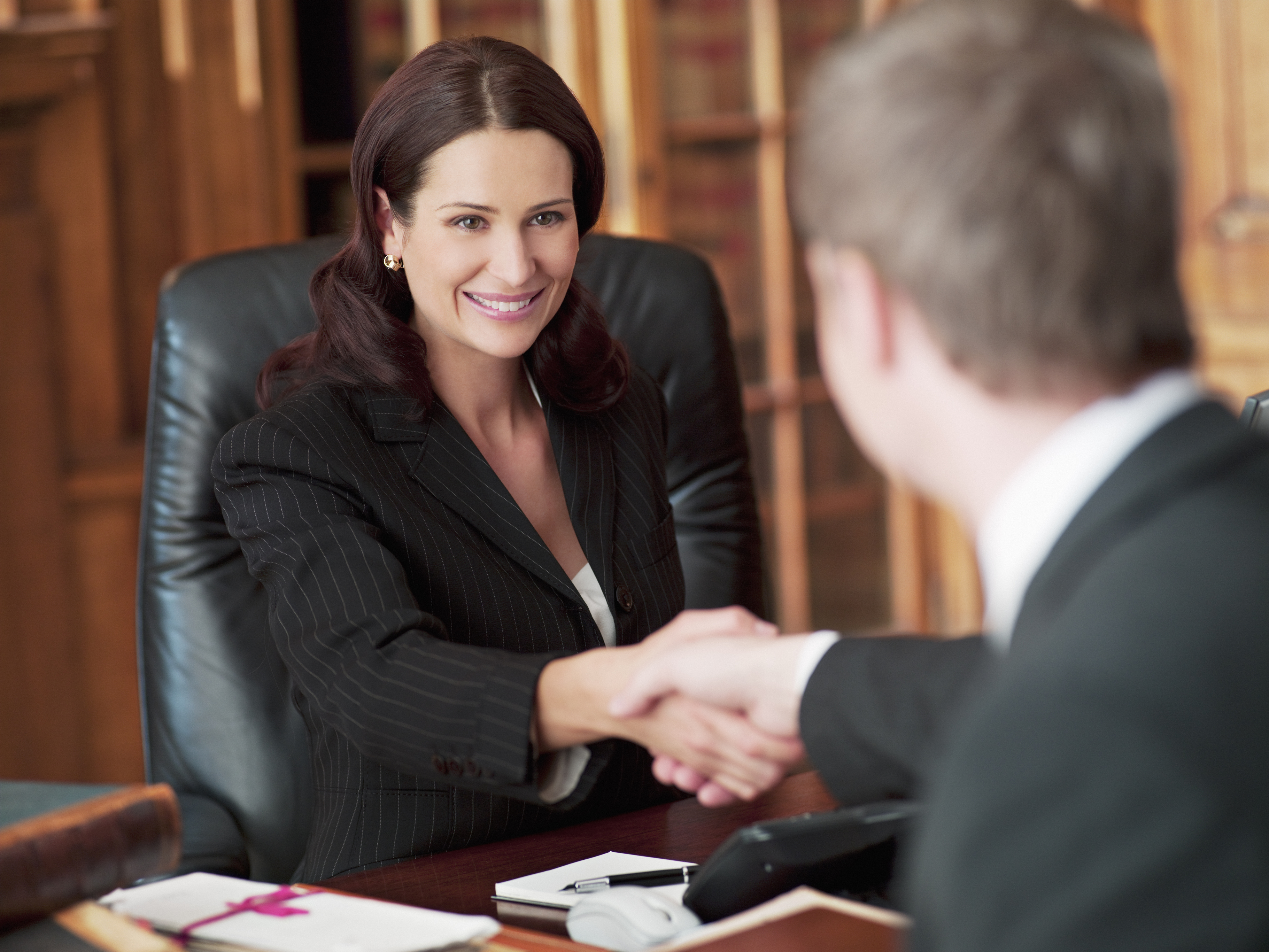 Smiling female lawyer shakes hands in office